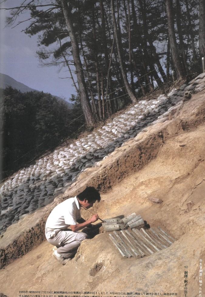 発掘調査で、銅鐸と銅矛が並んで出てきている様子