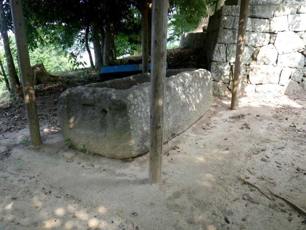 前方部の上にある神社のそばに置かれた石のお棺(かん)